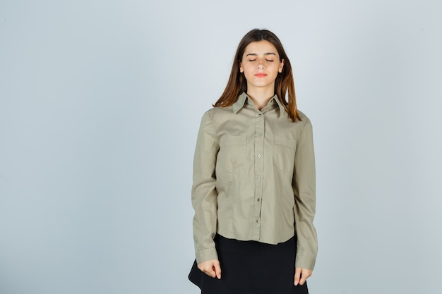 Young female shutting eyes in shirt, skirt and looking dreamy