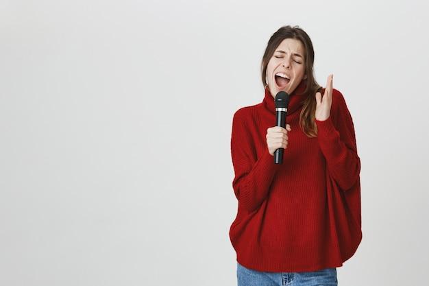 Молодая певица поет в микрофон