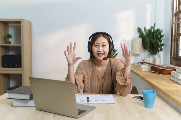 젊은 여성은 거실에 앉아 헤드셋을 쓰고 컴퓨터 공부와 아파트에서 이야기를 하고 있습니다.