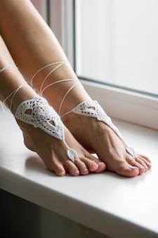 Молодая женщина сидит на фоне окна. ступни, подошвы и пальцы ног крупным планом.