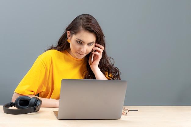 テーブルに座って、仕事、オンライン作業で最新のテクノロジーを使用して若い女性