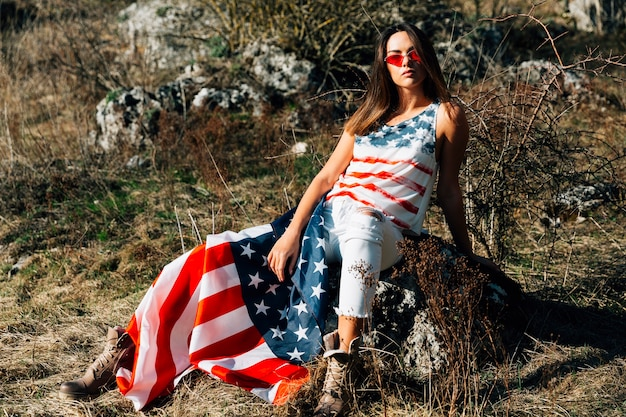 Young female sitting on stone with flag