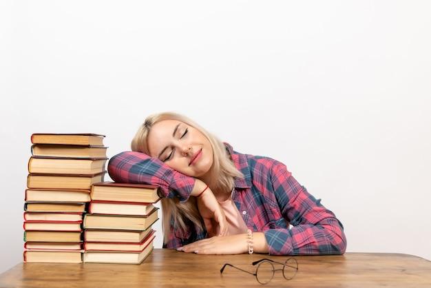 Молодая женщина сидит с книгами и пытается заснуть на белом