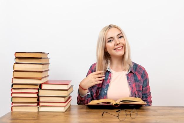 Молодая женщина сидит с книгами на белом