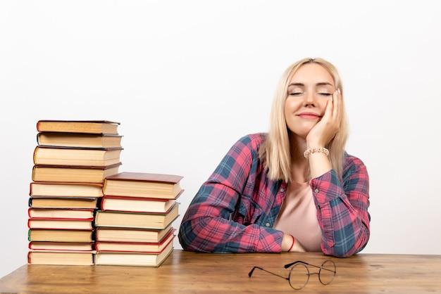 Giovane donna seduta con libri su bianco
