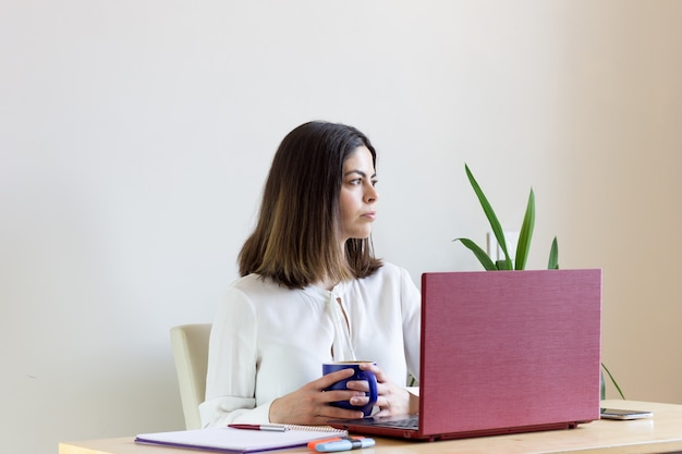 Young female sitting with a laptop and a cup of coffee working from home