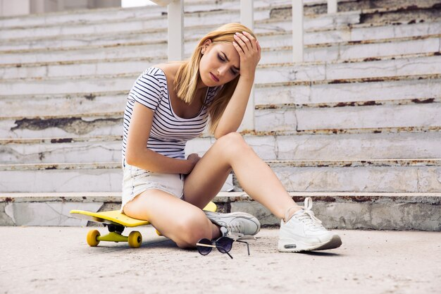 Young female skater having headache