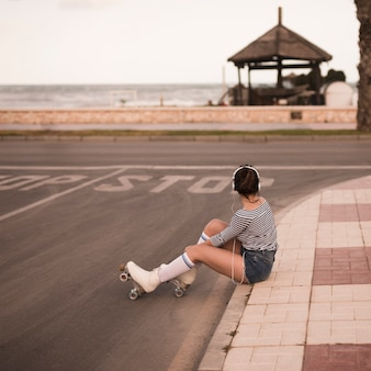 Young female skater sitting on sidewalk listening music on headphone looking away
