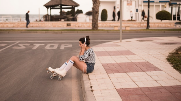 Young female skater sitting on sidewalk listening music on headphone