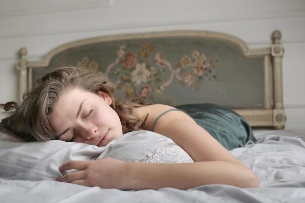 Giovane donna che dorme pacificamente nel letto la mattina