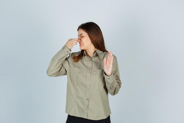 Giovane femmina che odora qualcosa di terribile, pizzicando il naso, mostrando il segnale di stop in camicia, gonna e guardando disgustato, vista frontale.
