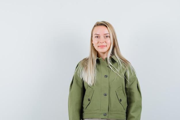 Giovane donna sorridente in giacca verde e che sembra carina. vista frontale.