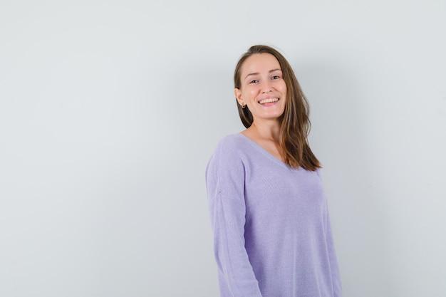 라일락 블라우스에 웃 고 긍정적 인 찾고 젊은 여성. 전면보기. 텍스트를위한 공간