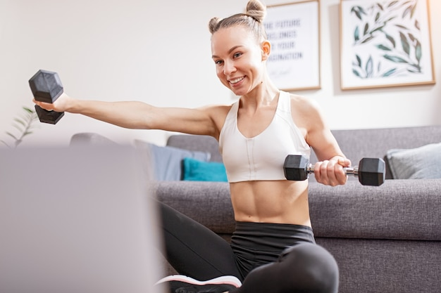Young female smiling and lifting dumbbells while watching fitness course on laptop during self isolation at home