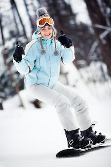 Молодая сноубордистка показывает палец вверх во время скольжения по склону