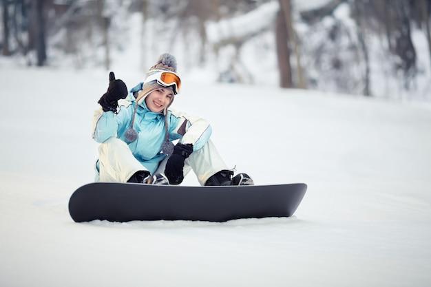 斜面に座って親指を上に表示して若い女性スノーボーダー
