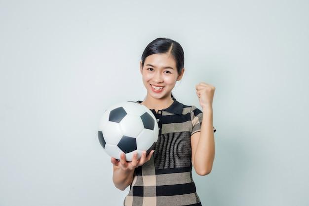 若い女性のサッカーファン幸せな手がサッカーを手に持って、幸せな人間の感情の概念。