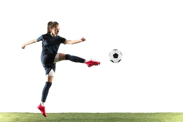 Giovane calcio femminile o giocatore di football con i capelli lunghi in abbigliamento sportivo e stivali calciare la palla per l'obiettivo nel salto isolato su sfondo bianco. concetto di stile di vita sano, sport professionistico, hobby.