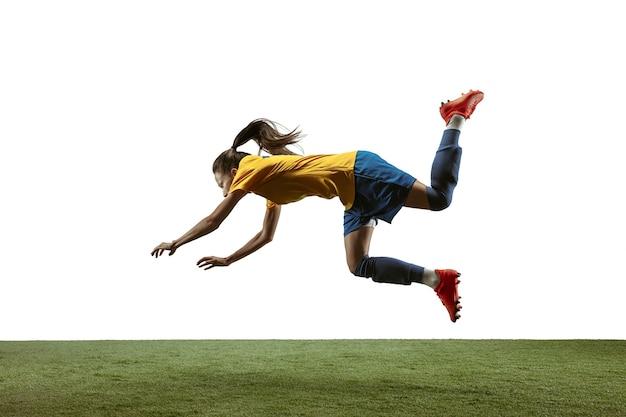 긴 머리에 운동복을 입고 부츠를 신은 젊은 여성 축구 선수나 축구 선수는 흰색 배경에서 점프 목표를 위해 공을 차고 있습니다. 건강한 생활 방식, 프로 스포츠, 운동, 운동의 개념.