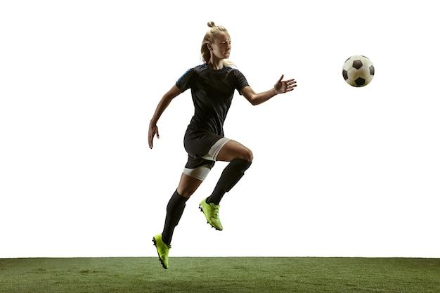 Молодой женский футбол или футболист с длинными волосами в спортивной одежде и ботинках, пинающий мяч для цели в прыжке на белом фоне. концепция здорового образа жизни, профессионального спорта, движения, движения.