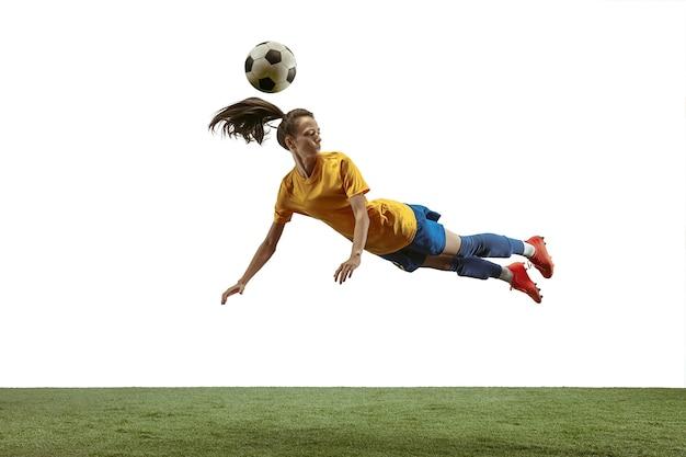 スポーツウェアとブーツのキックボールで長い髪の若い女性のサッカーまたはサッカー選手