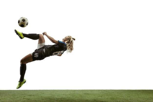 Молодая женщина-футболист или футболистка с длинными волосами в спортивной одежде и ботинках, пинающая мяч