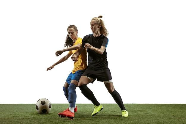 긴 머리에 운동복을 입고 흰색 바탕에 부츠 훈련을 하는 젊은 여성 축구 선수. 건강한 생활 방식, 프로 스포츠, 운동, 운동의 개념. 목표를 위해 싸워라.