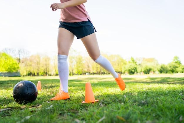 フィールドで練習して若い女性のサッカー選手