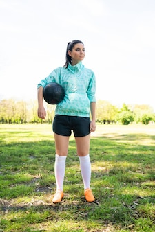 Young female soccer player standing on field holding ball