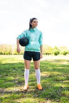 Молодая женщина-футболист, стоя на поле, держа мяч