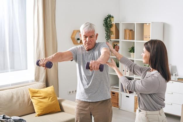 Молодая женщина-социальный работник помогает пожилому мужчине в спортивной одежде, тренируясь с гантелями в домашней обстановке
