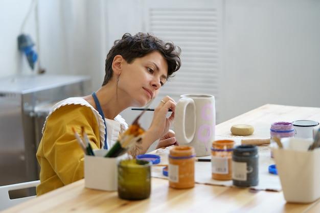 젊은 여성은 도자기 작업을 하는 세라믹 스튜디오에서 시간을 보내고 예술 수업을 즐깁니다.