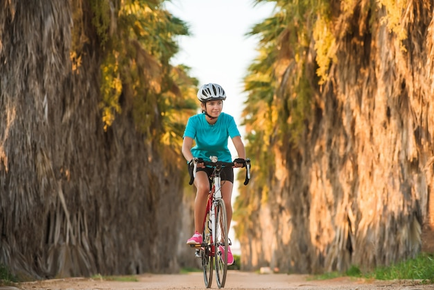 Young female sporty cyclist riding bike on road with palms