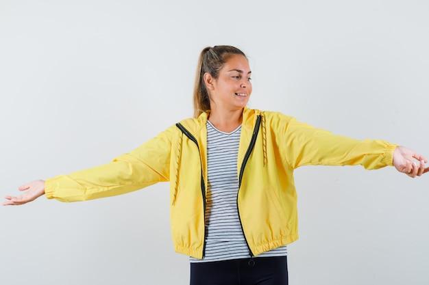 Молодая женщина разводит руками в куртке, футболке и выглядит мирно, вид спереди.
