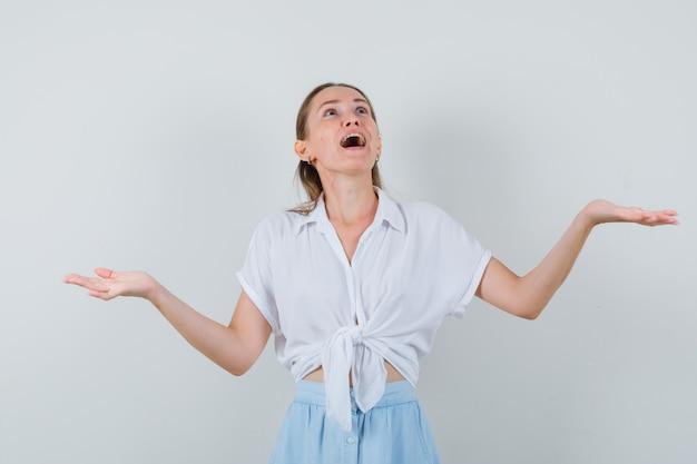 Giovane donna che allarga le braccia, alzando lo sguardo in camicetta e gonna e guardando allegra