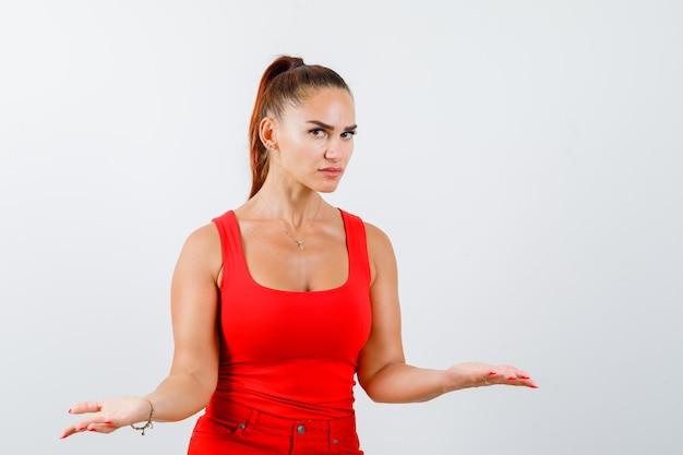 若い女性は赤いタンクトップ、ズボンで脇に手のひらを広げ、真剣に見える、正面図。