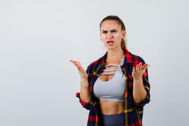 若い女性は、クロップトップ、市松模様のシャツ、パンツで無知なジェスチャーで手のひらを広げ、無力に見える、正面図。
