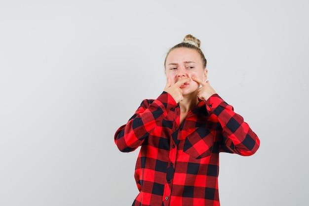 Giovane donna che stringe il suo brufolo sulla guancia in camicia a quadri, vista frontale.