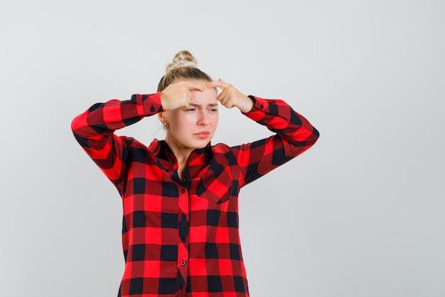 Giovane donna stringendo il suo brufolo sulla fronte in camicia a quadri, vista frontale.