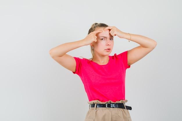 Giovane donna che stringe il suo brufolo sulla fronte in t-shirt, pantaloni, vista frontale.