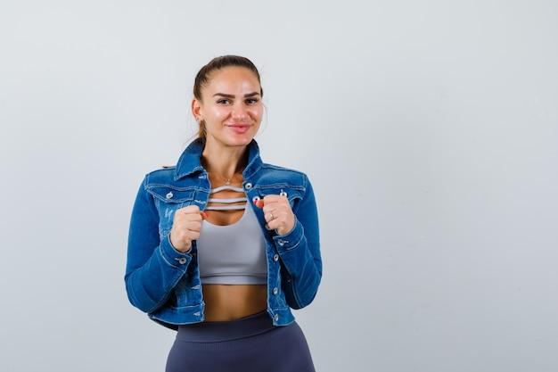 Giovane donna in piedi in posa di lotta in top corto, giacca, pantaloni e sembra sicura. vista frontale.
