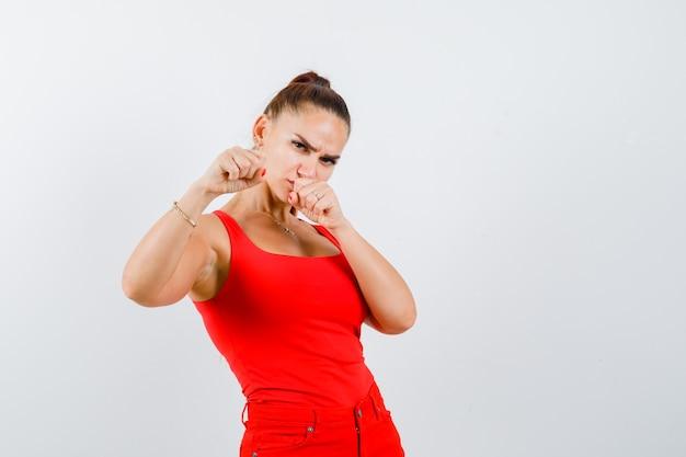 赤いタンクトップ、パンツ、自信を持って、正面図で戦闘ポーズで立っている若い女性。