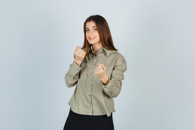 シャツ、スカート、陽気に見える戦闘ポーズで立っている若い女性