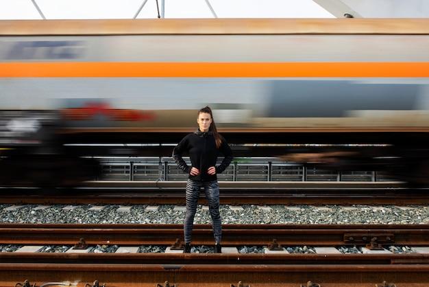 Молодая женщина, стоящая перед движущимся поездом