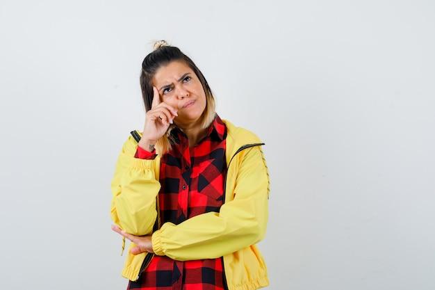 思考ポーズで立っている若い女性、市松模様のシャツ、ジャケットで目をそらし、困惑しているように見える、正面図。