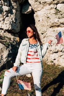 Young female standing in mountains with american flags