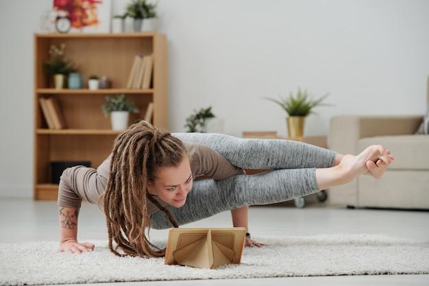 Молодая женщина, стоящая на руках в одной из поз йоги перед экраном тачпада, тренируясь дома