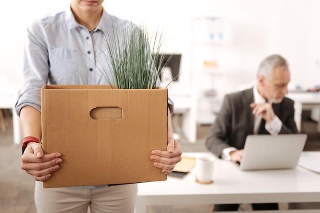 事務所を離れるときに大きな箱を持って前景に立っている若い女性