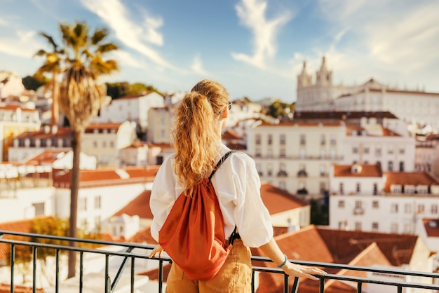 Young female standing on a platform surrounded by fences and observing lisbon at daytime in portugal