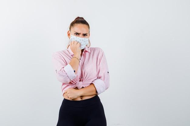 Giovane donna in piedi in posa spaventata in camicia, pantaloni, mascherina medica e sembra stressata. vista frontale.